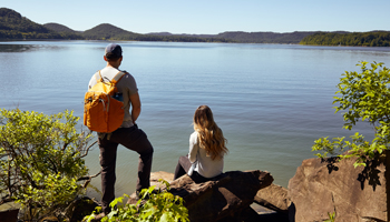 guy with back pack on looking at lake and girl sitting on rock beside him